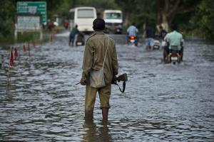 Asian Image: A forest guard stands to slow down vehicles on a flooded highway as animals cross the highway to take shelter on highlands in Kaziranga National Park, east of Gauhati, northeastern Assam state, India. Vast tracts of the park, home to the rare one-horned rhino, and another wildlife reserve were under water. Forest officials said they have found the remains of at least one rhino that had drowned in the flooding in the park. (AP Photo/Anupam Nath).